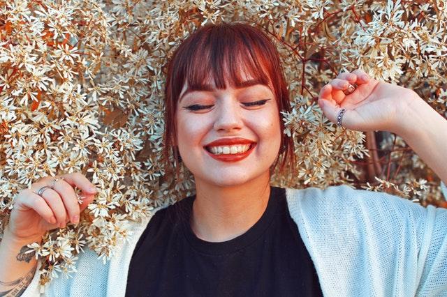 Usmiata žena s červenými perami medzi bielymi kvetmi.jpg