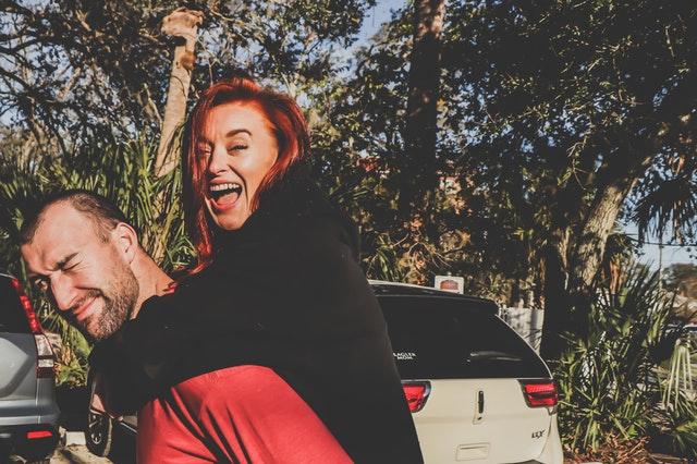 Žena na chrbte muža sa usmieva.jpg