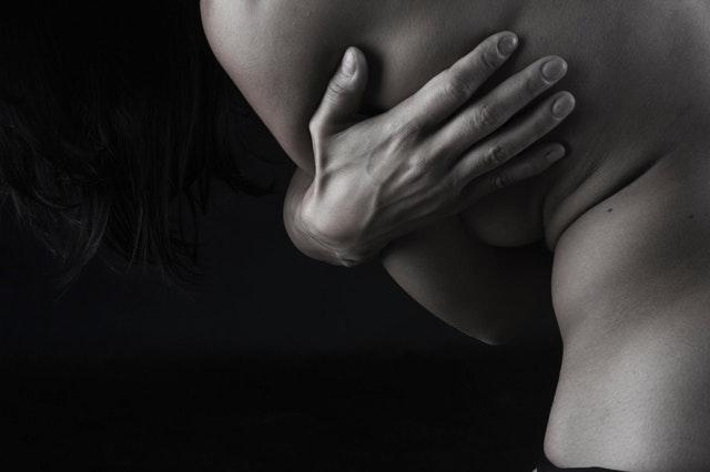 Nahá žena s čiernymi vlasmi sa drží za chrbát.jpg